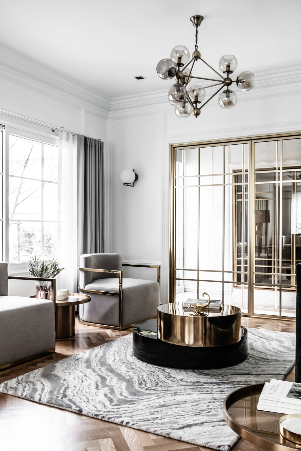 These are then topped with a modern decorative chandelier over the coffee table that stands out against the light area rug.