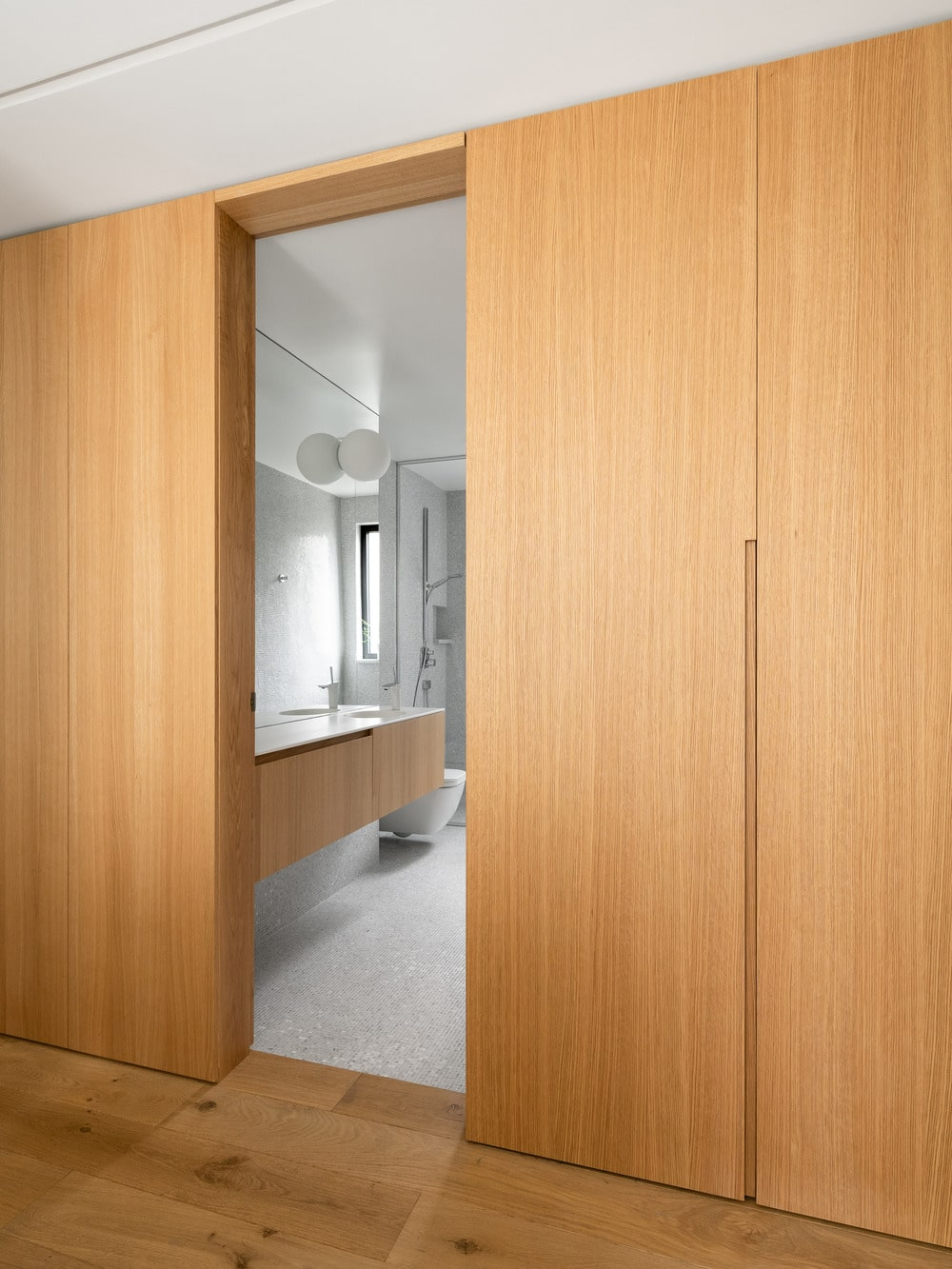 The open door of the bathroom shows the vanity has the same wooden tone as the walls outside.
