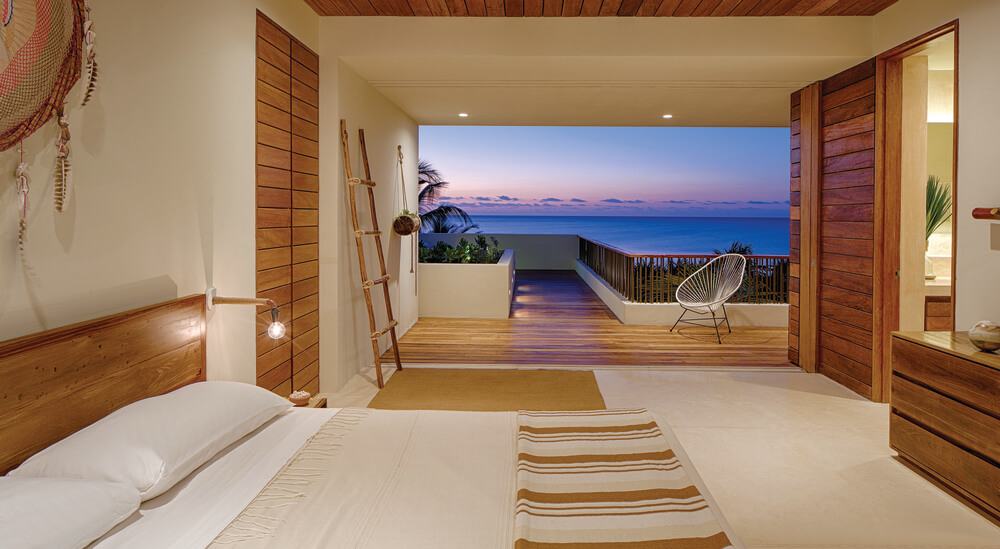 This bedroom has a large bed, a bathroom with a wooden sliding door and a view through the balcony.