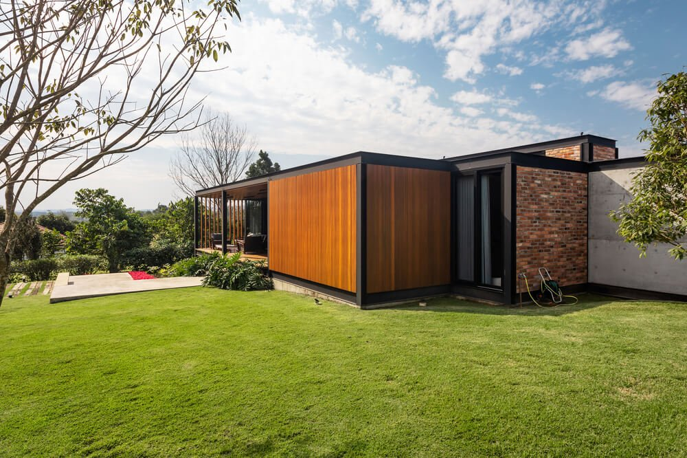 This side of the house shows that the house has three exteriors tone with its concrete, brick and wooden tones,