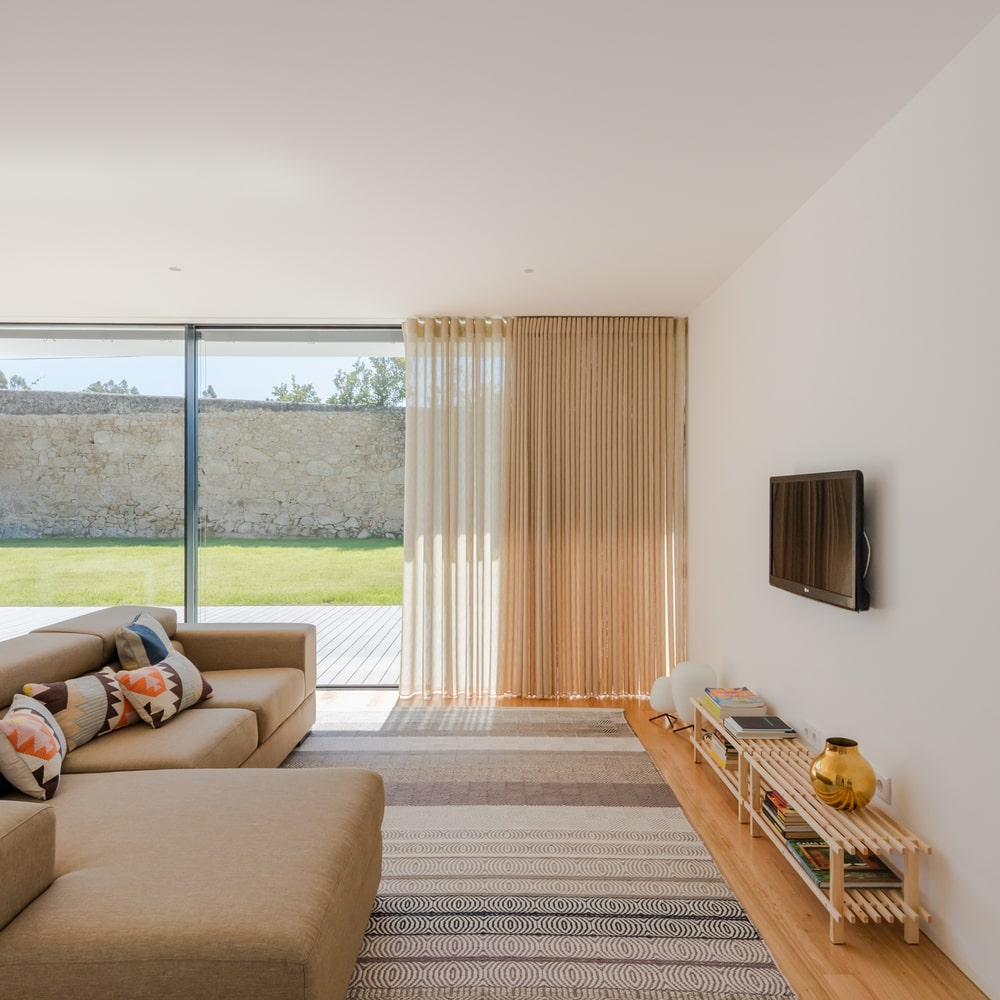 The living room has a large L-shaped sectional beige sofa on a patterned area rug.