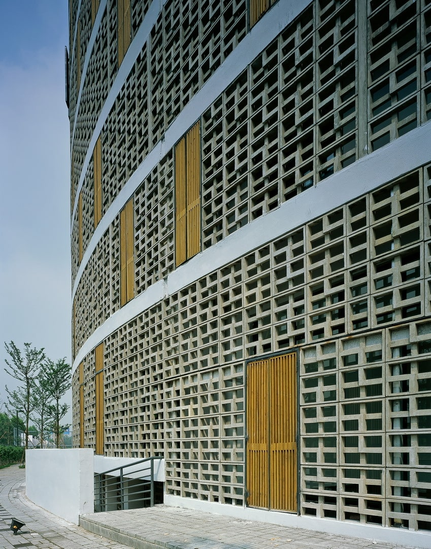 This is a close look at the side of the building showcasing the patterned concrete wall panels, windows and a set of steps leading to the basement floors.
