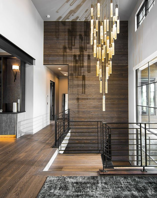 A glass cascading chandelier hanging from the soaring ceiling illuminates the foyer.