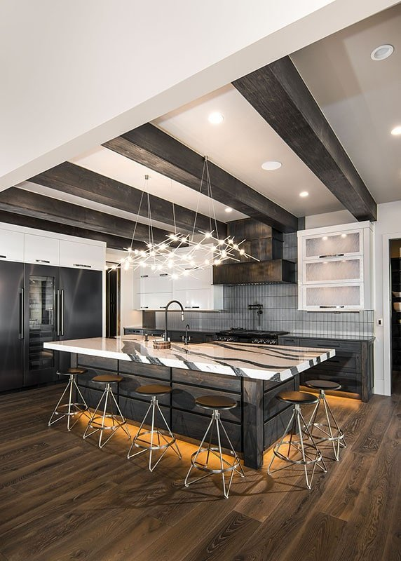 The kitchen is brightened by recessed lights, strip lighting, and contemporary pendants that hang from the beamed ceiling.