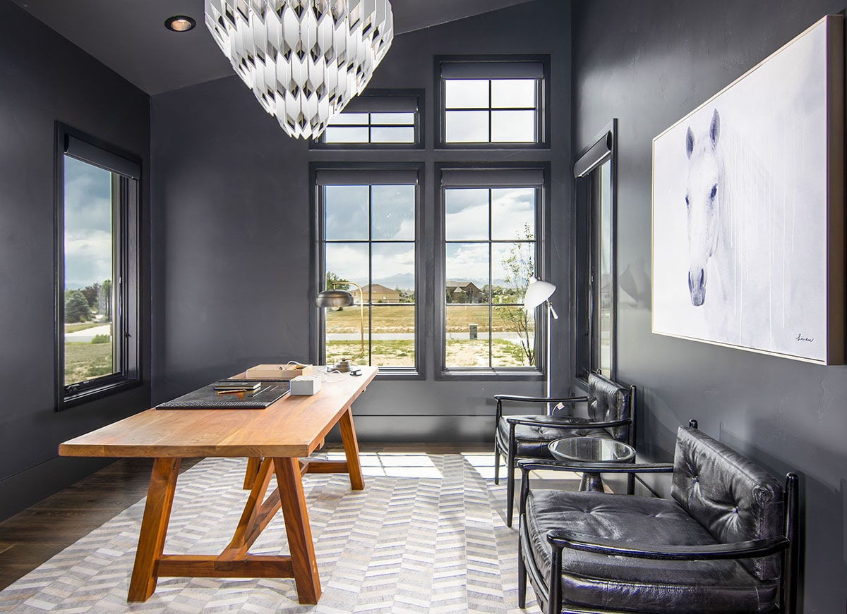 The home office is furnished with black leather armchairs, a wooden desk, and a unique chandelier.