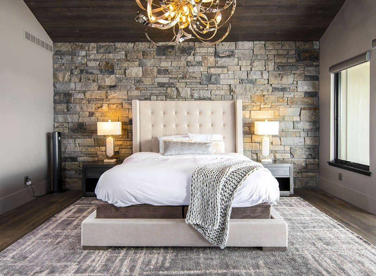 Primary bedroom with a chrome chandelier, and a tufted wingback bed flanked by wooden nightstands.
