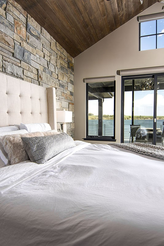 A close-up look at the primary bedroom showing its vaulted ceiling, stone accent wall, and glass sliding doors that lead to the covered deck.