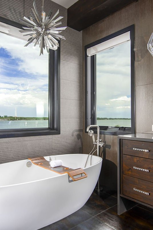 The soaking tub is well-lit by a sputnik chandelier and natural light from the picture windows.