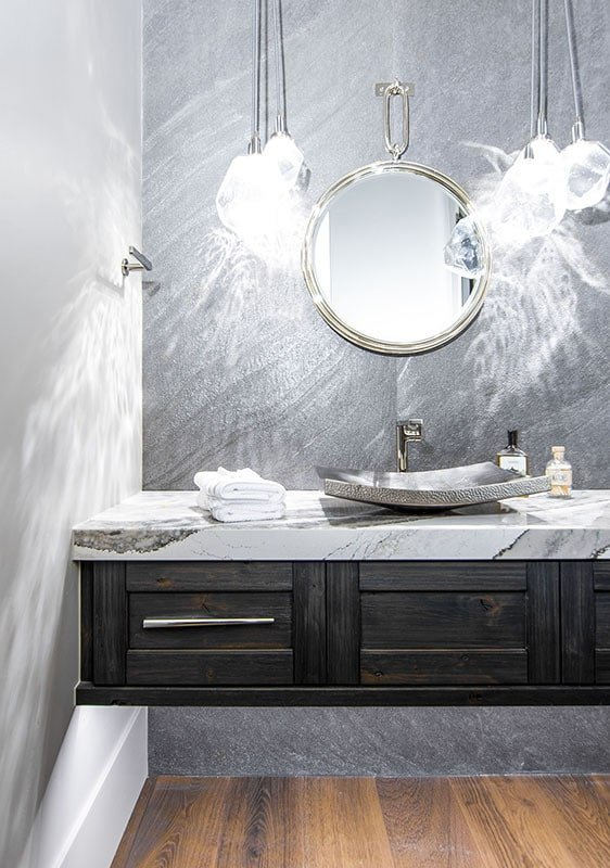 The powder room features a marble top vanity with a round mirror and an elegant vessel sink.