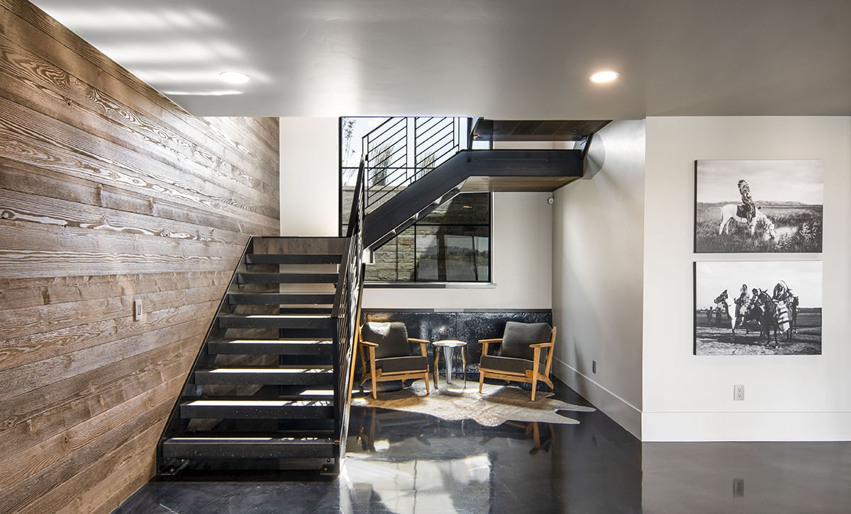 Underneath the stairs is a sitting area with cushioned armchairs over a cowhide rug.