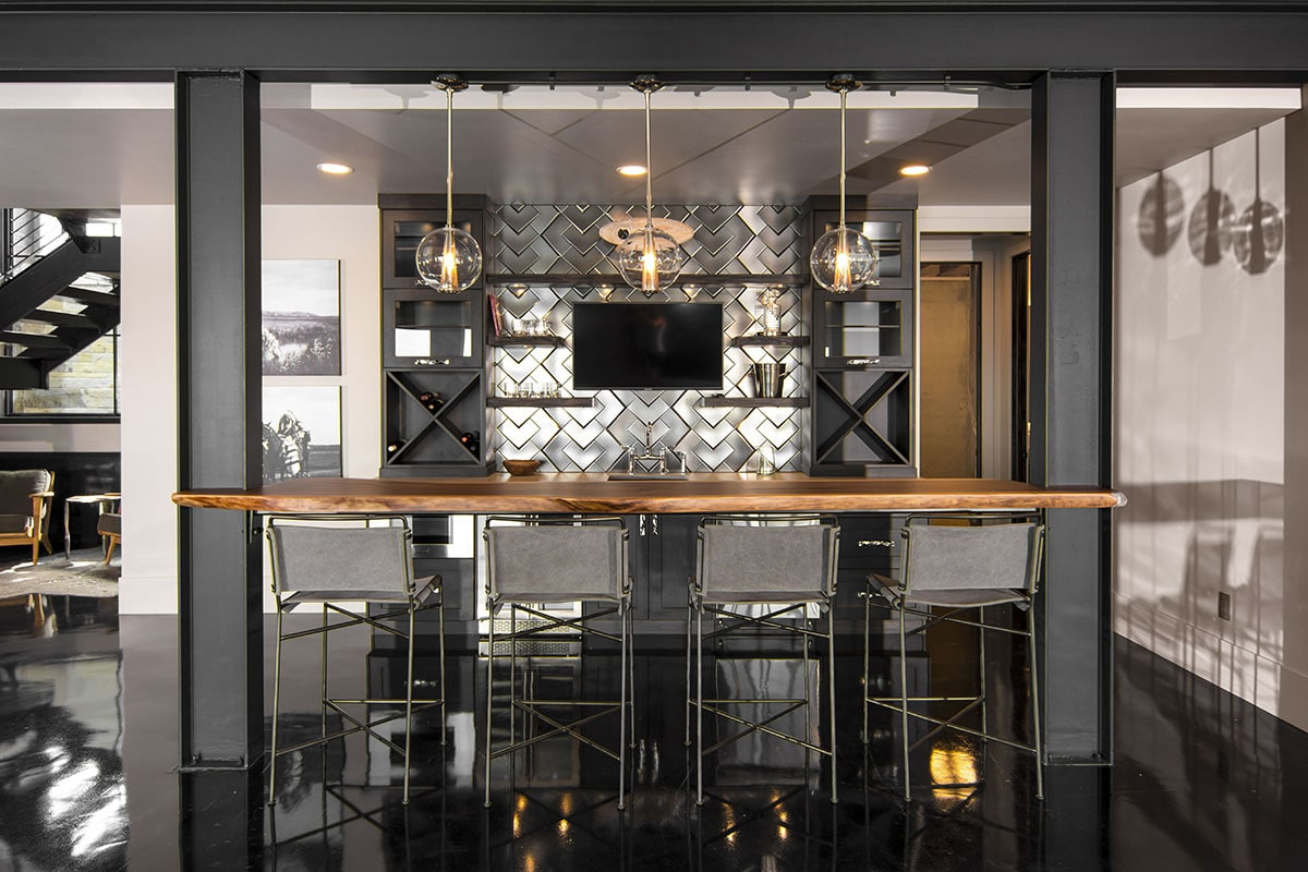 There's also a wet bar with built-in wine racks and a wooden counter lined with metal bar stools.