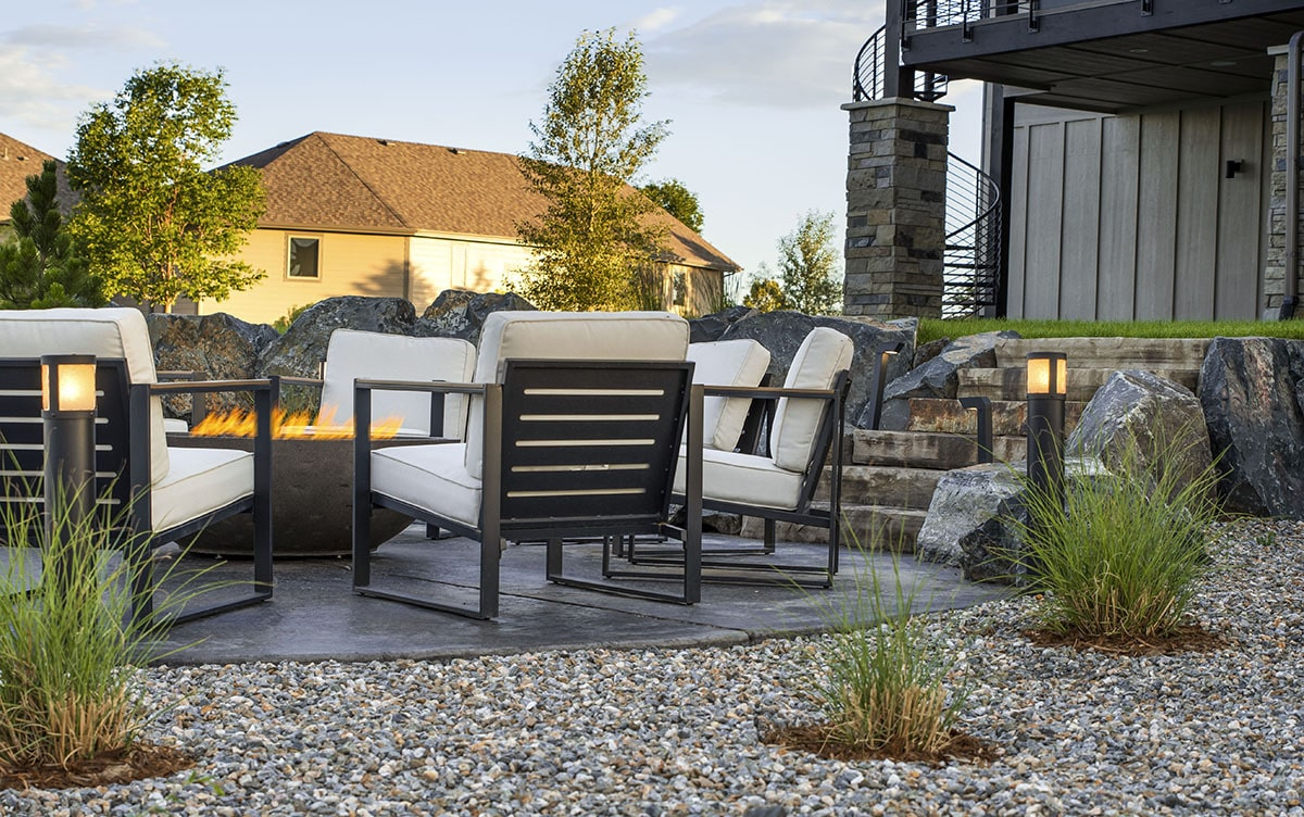 A stone staircase leads to the fire pit seating area.