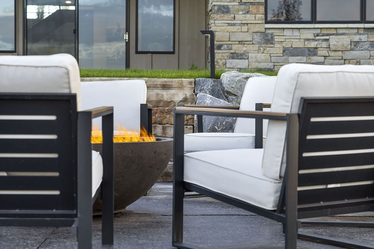 A close-up look at the cushioned chairs and fire pit bowl.