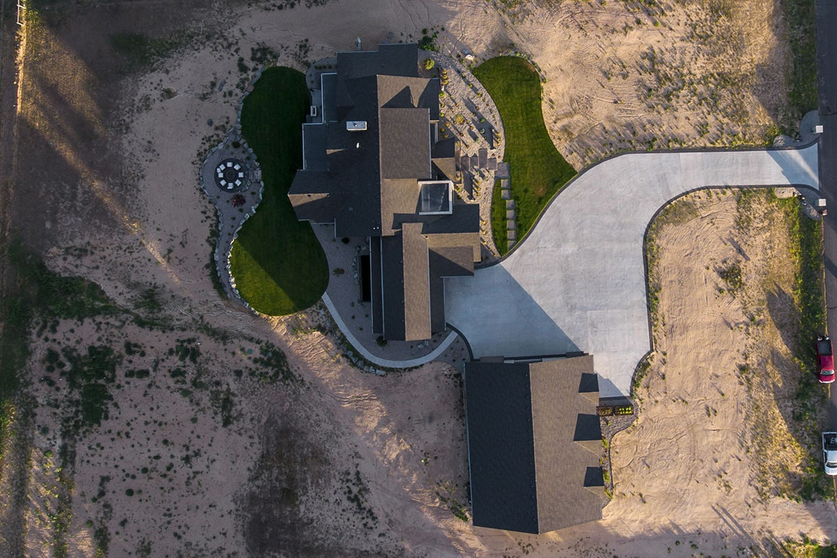 Bird's eye view of the modern mountain home showing the main house and outbuilding connected by a concrete driveway.
