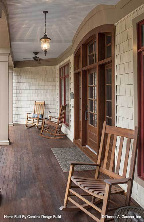 The covered porch is furnished with wooden rocking chairs and a textured rug.The covered porch is furnished with wooden rocking chairs and a textured rug.