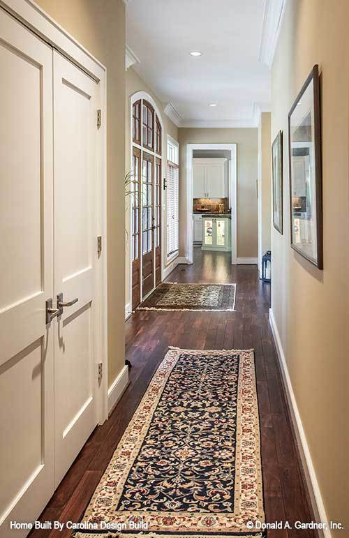 A hallway with a patterned runner leading to the bedrooms.