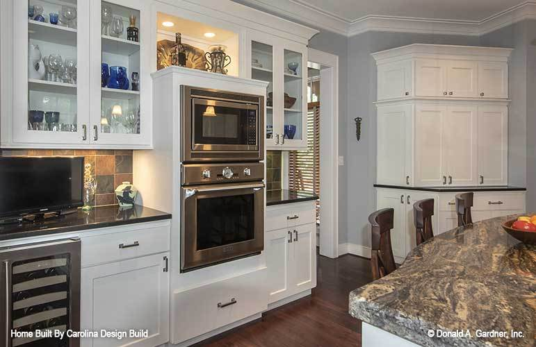 Kitchen with white and glass front cabinets, stainless steel appliances, granite countertops, and a breakfast bar.