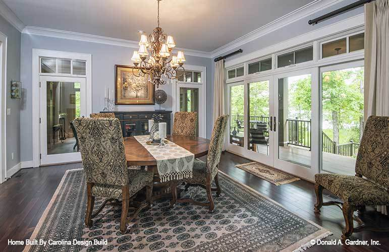 Dining room with an ornate chandelier, a round dining set, and direct access to the covered porch.
