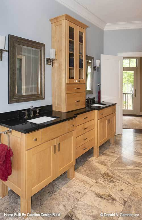The primary bathroom features his and her vanities separated by a wooden cabinet.