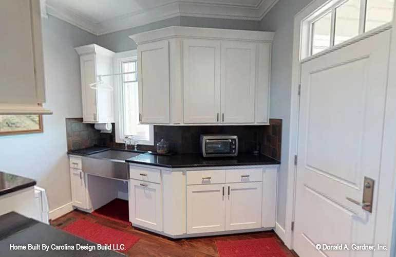 The laundry room is equipped with quartz countertops, white cabinets, and a utility sink.