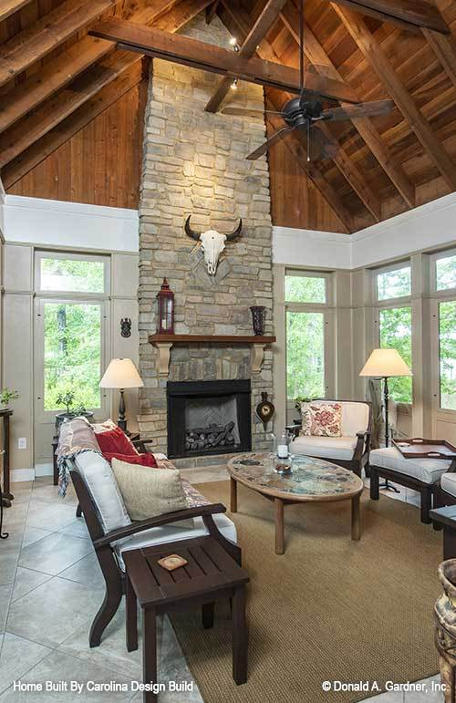 Sunroom with cushioned seats, a stone fireplace, and a cathedral ceiling clad in wood planks.