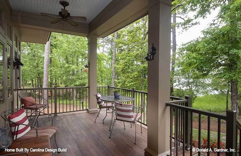 Rear porch with metal chairs, wooden railings, and beige pillars.