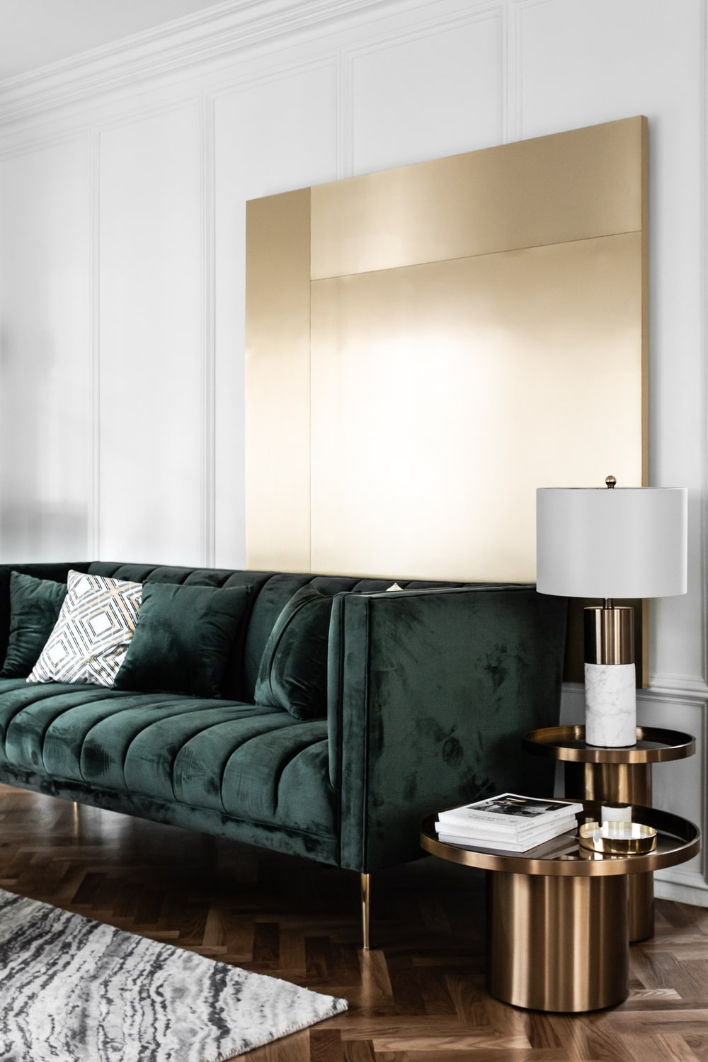 The sofa has a couple of end tables on one side with one taller to support the lamp.