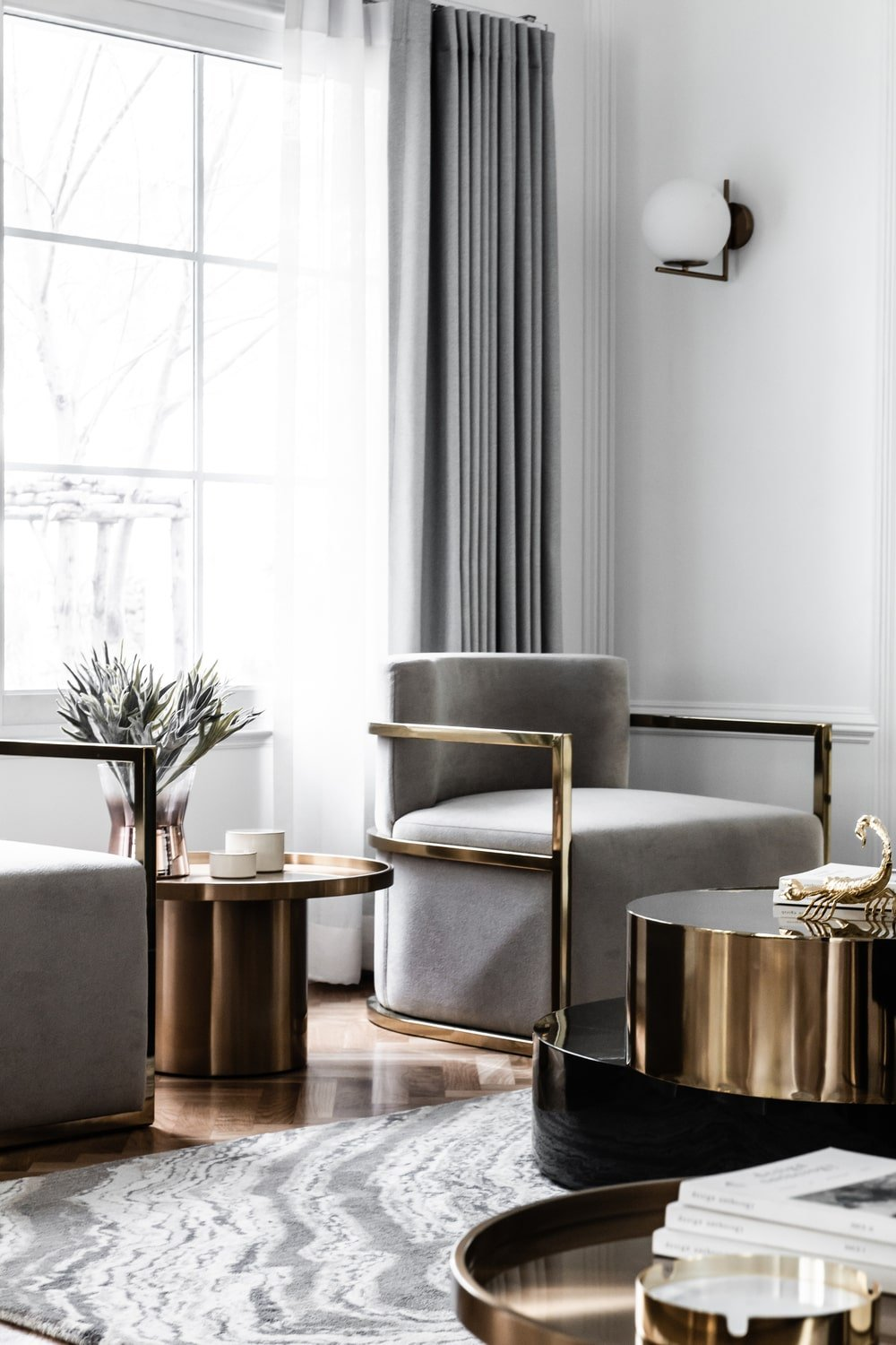 The two cushioned arm chairs across from the sofa has shiny metallic frames paired with a small round side table.