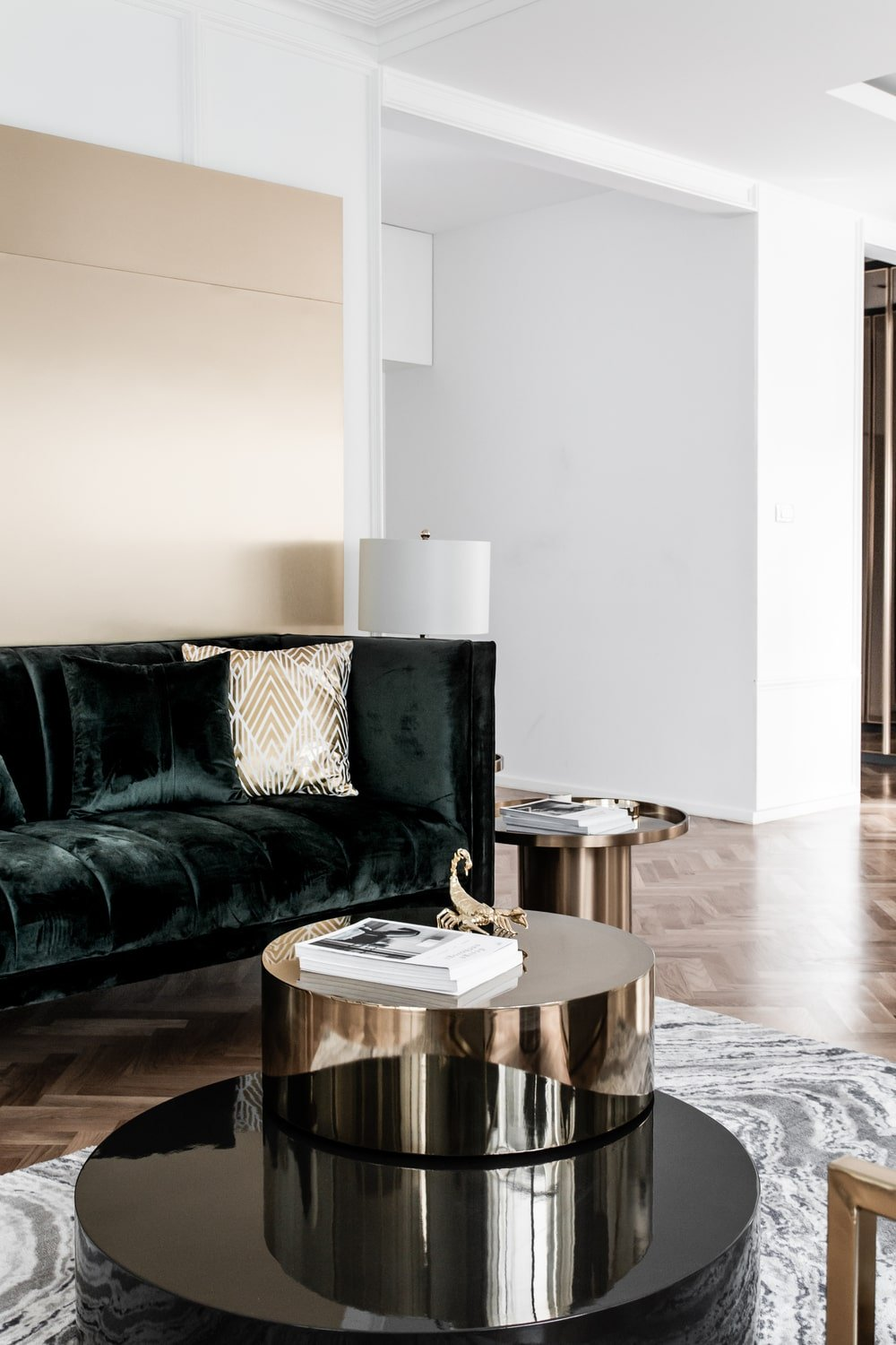 The metallic tone of the second tier of the coffee table matches well with the black velvet sofa.