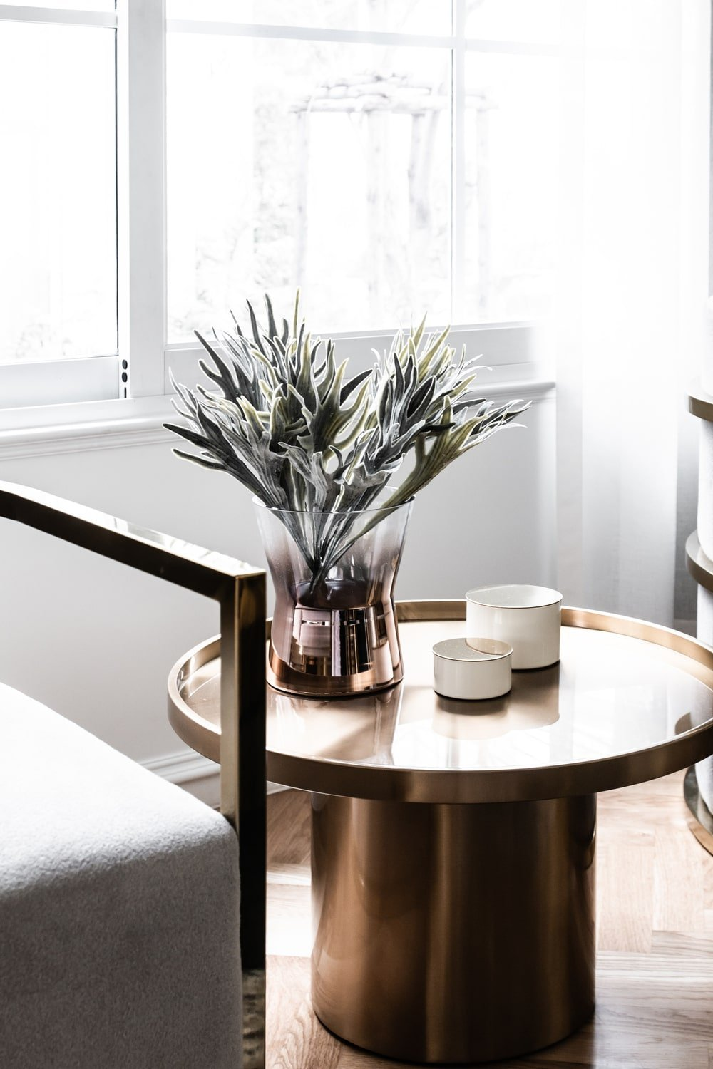 This is a close look at the small round side table of the arm chairs with a shiny metallic tone to it brightened by the window.