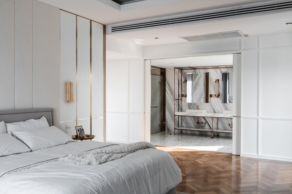 The bed stands out against the herringbone hardwood flooring that leads to the bathroom.