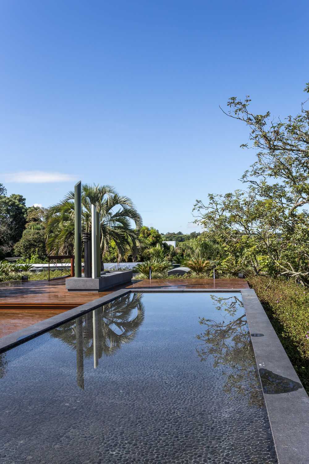 A few steps from the concrete structure is the small rooftop pool with a dark tone to it.