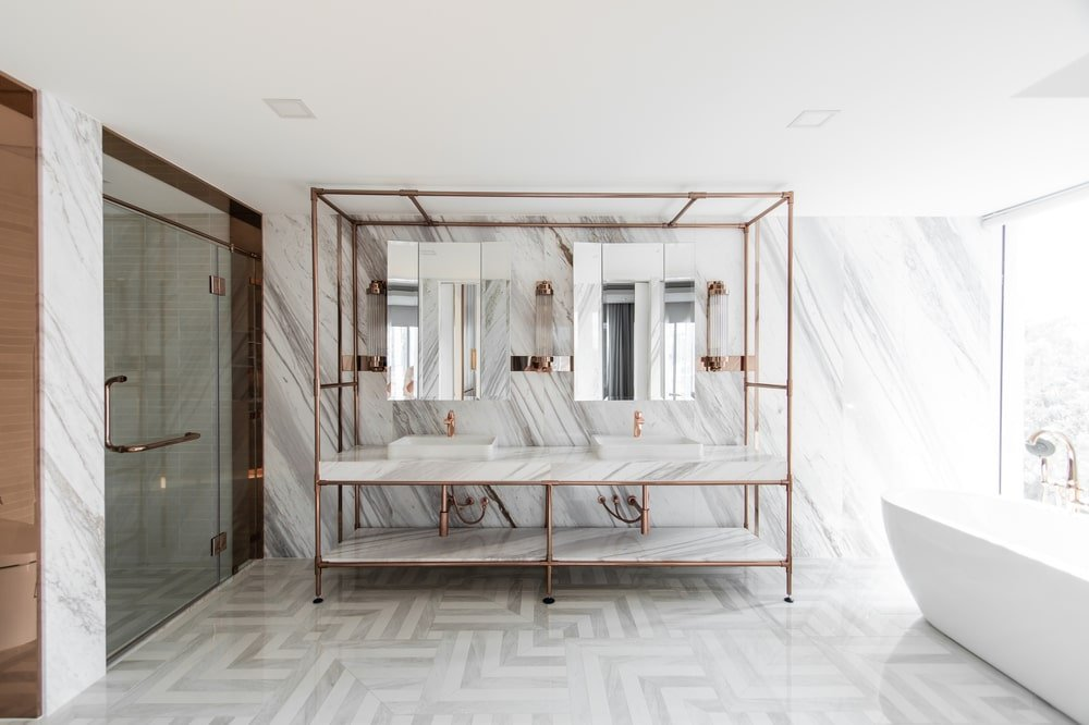The bathroom has a large two-sink vanity supported by a system of golden frames that stand out against the white marble wall.