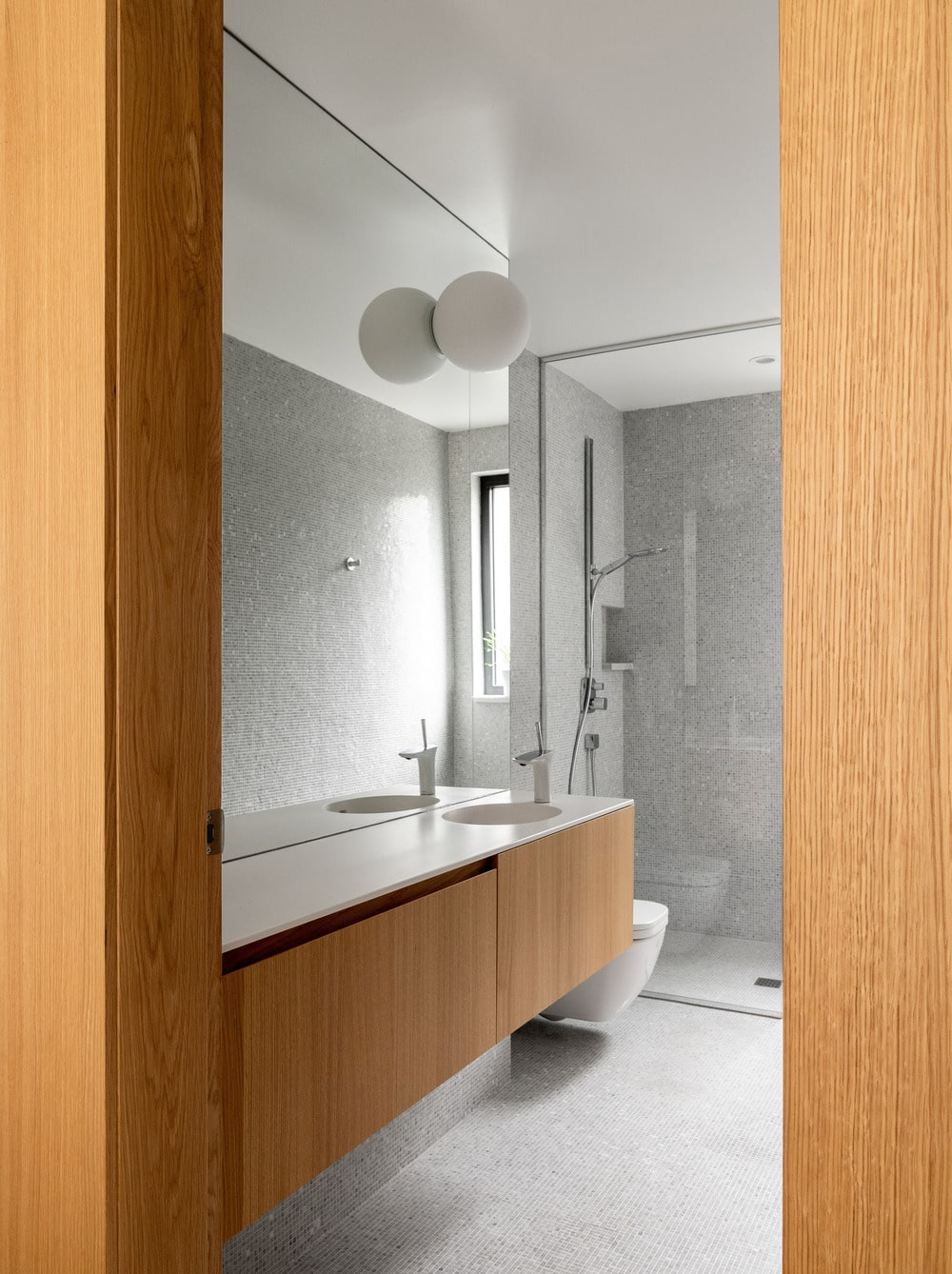 Next to the floating wooden vanity is the toilet, followed by the shower area.