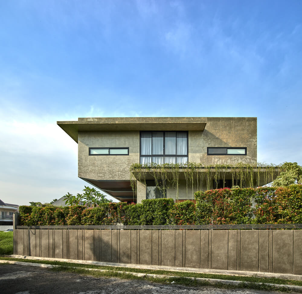 This is an exterior view of the house elevation showcasing the large glass wall on the upper level.