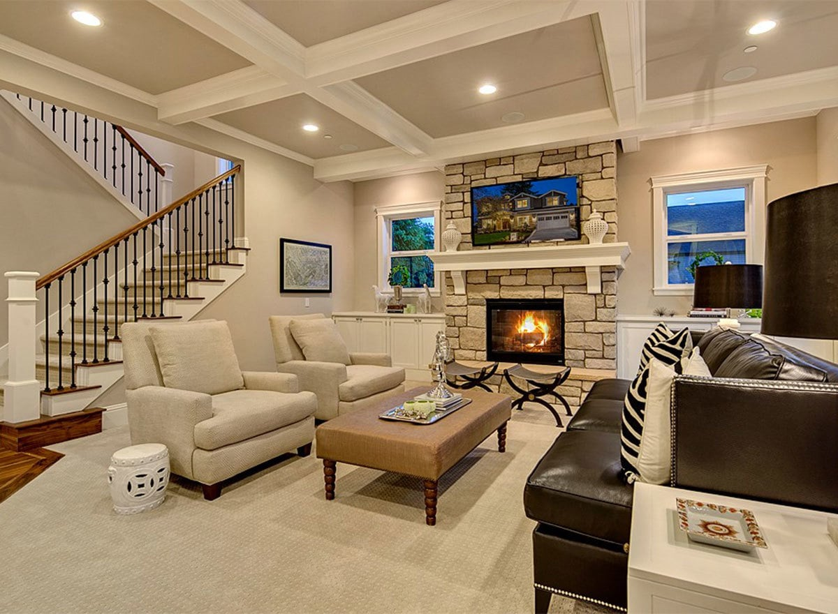 Living room with coffered ceiling, carpet flooring, leather sofa, beige upholstered chairs, and a fireplace.