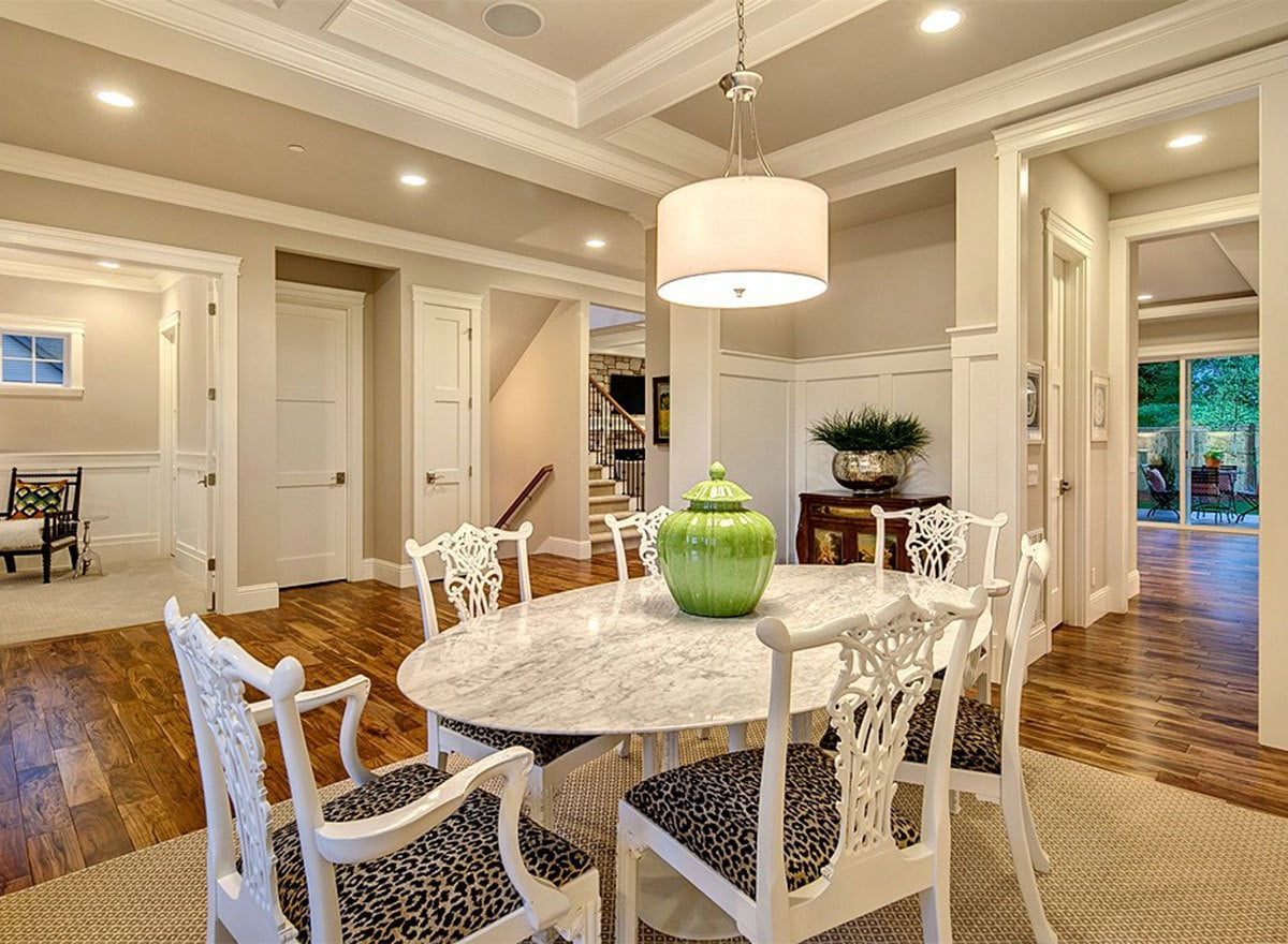 Recessed ceiling lights and a drum chandelier illuminate the dining room.