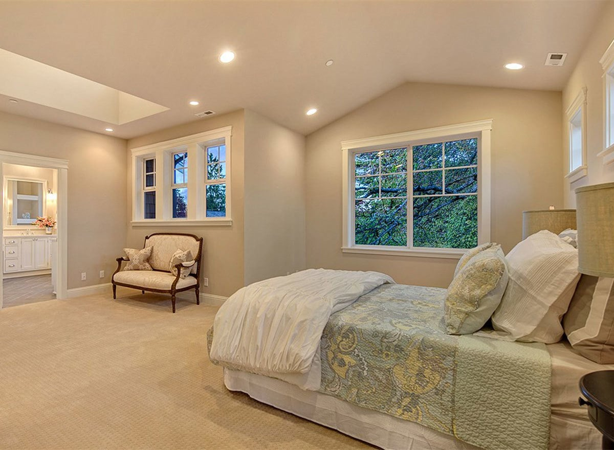 Primary bedroom with carpet flooring, vaulted ceiling, white-framed windows, a sitting area, and a comfy skirted bed.