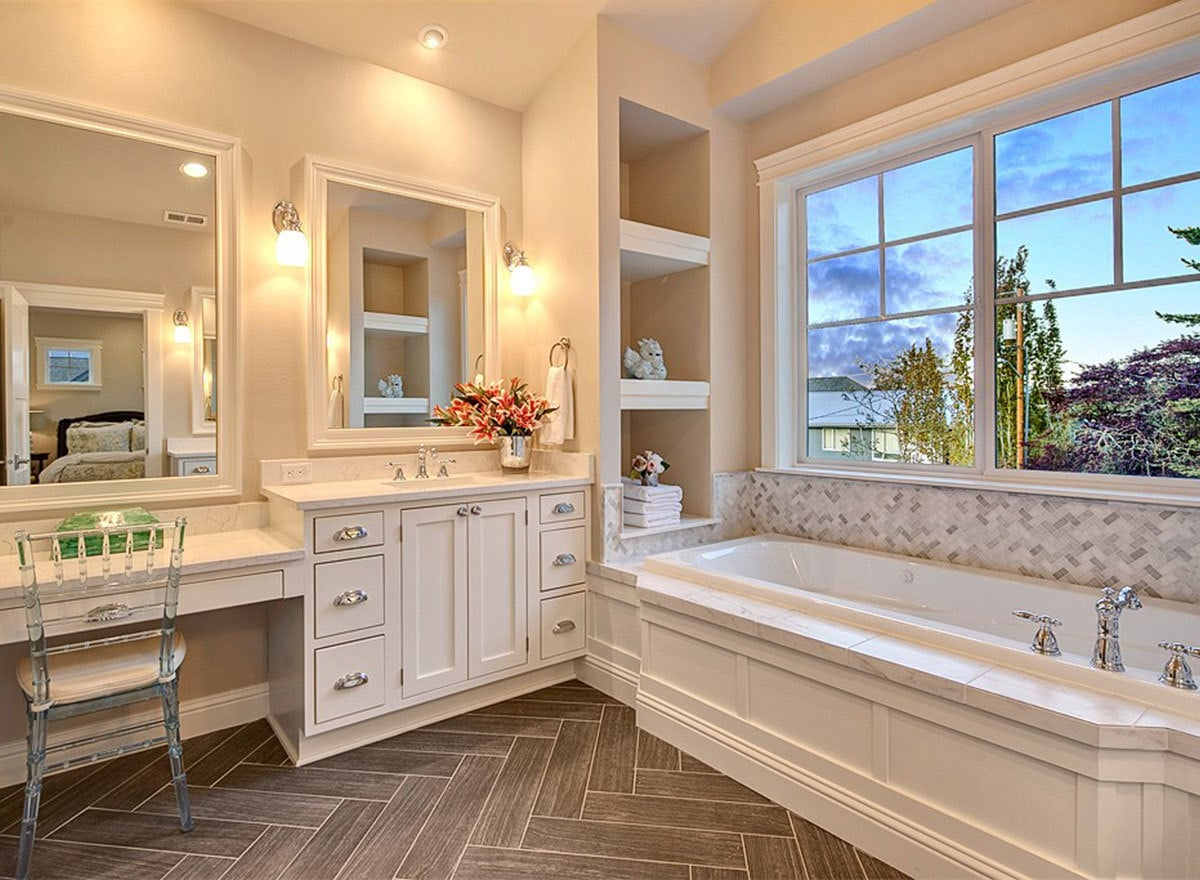 An elegant glass chair complements the bathroom vanity.