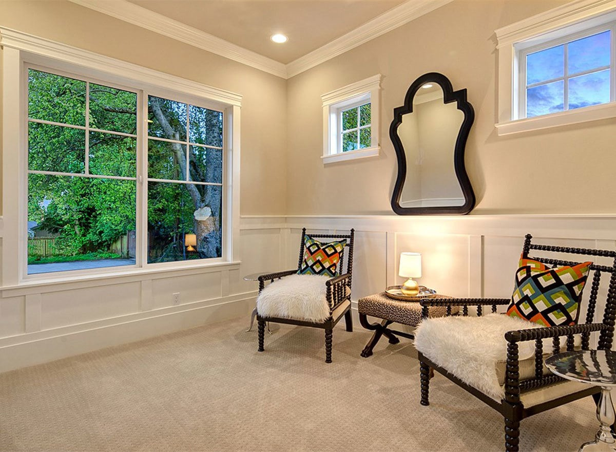 Den with dark wood armchairs and beige walls adorned with white wainscoting and a decorative mirror.