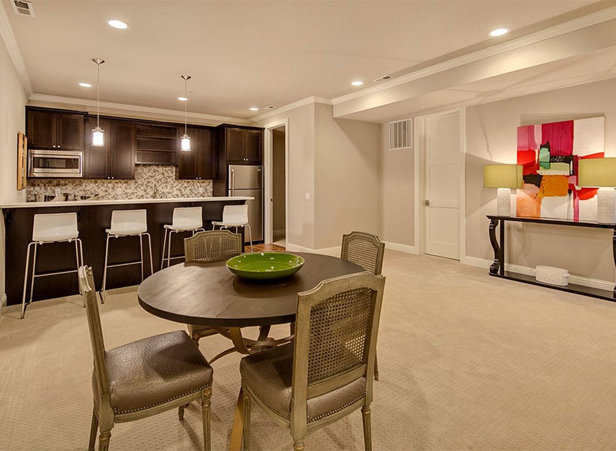 A round dining set and a wet bar complete the recreation room.