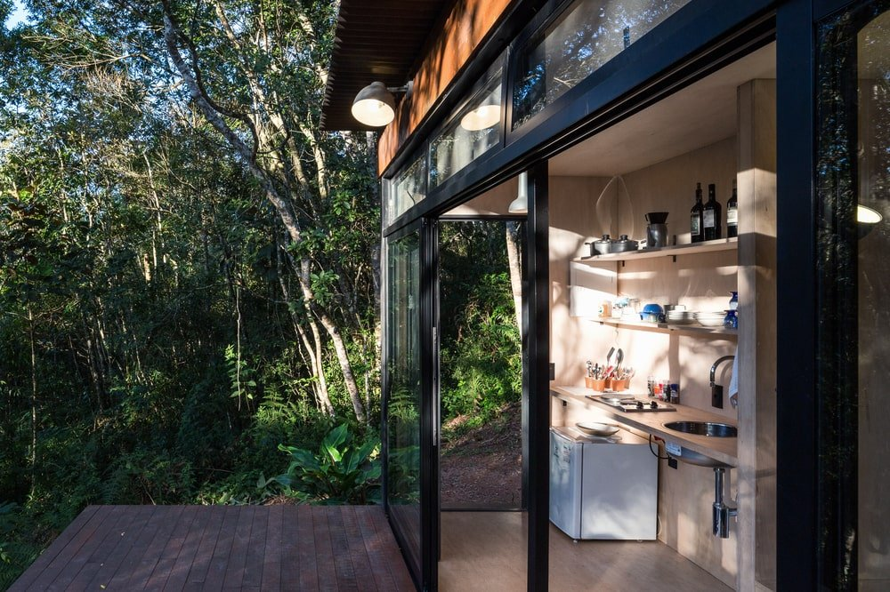 This is a view of the kitchen area of the house from the vantage of the terrace that has a wooden deck flooring.