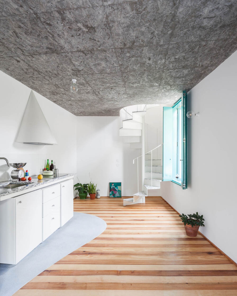 The kitchen has a counter on the isde by the wall that has built-in cabinets and drawers topped with a simple vent hood above.