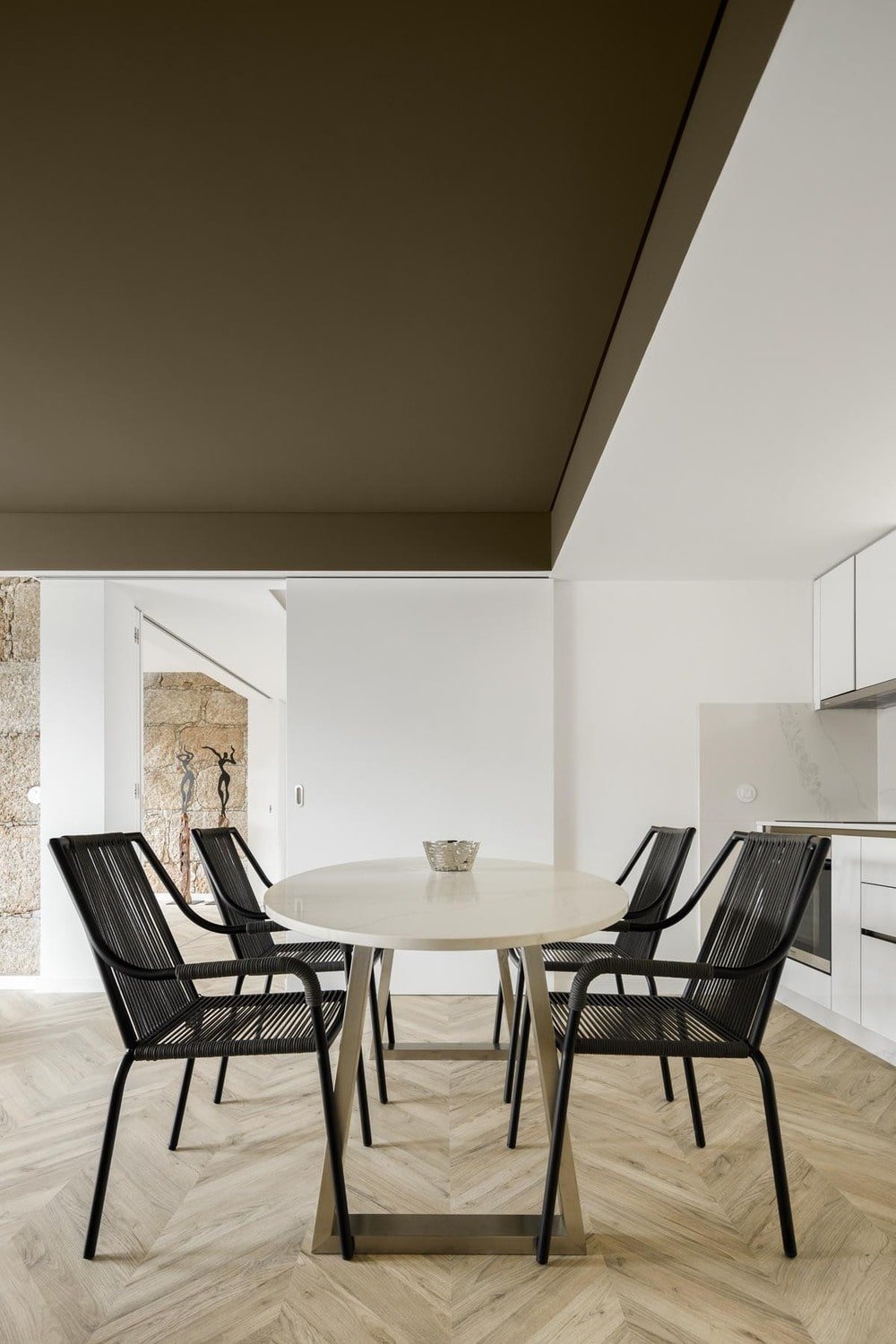 On the side of this sliding door is the dining area that has a white dining table contrasted by the black chairs surrounding it.