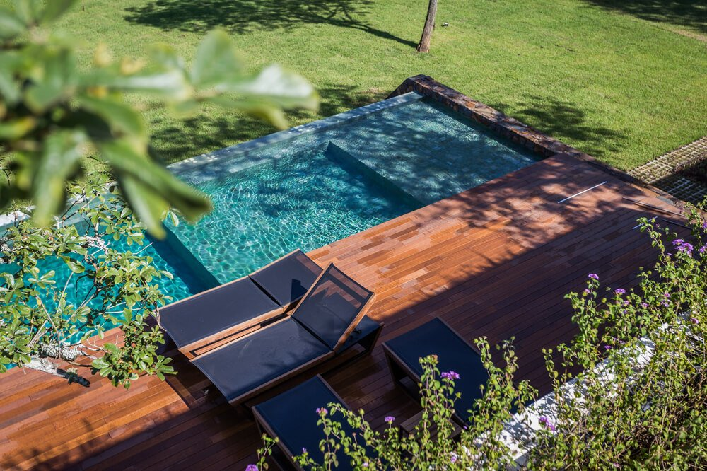 The side of the pool has a wooden flooring fitted with lounge chairs.