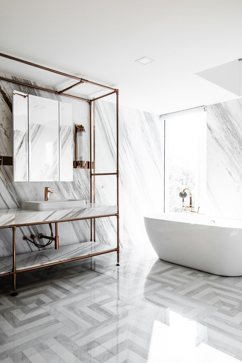 The bathroom has light gray patterned tiles with a shiny tone to match the marble.