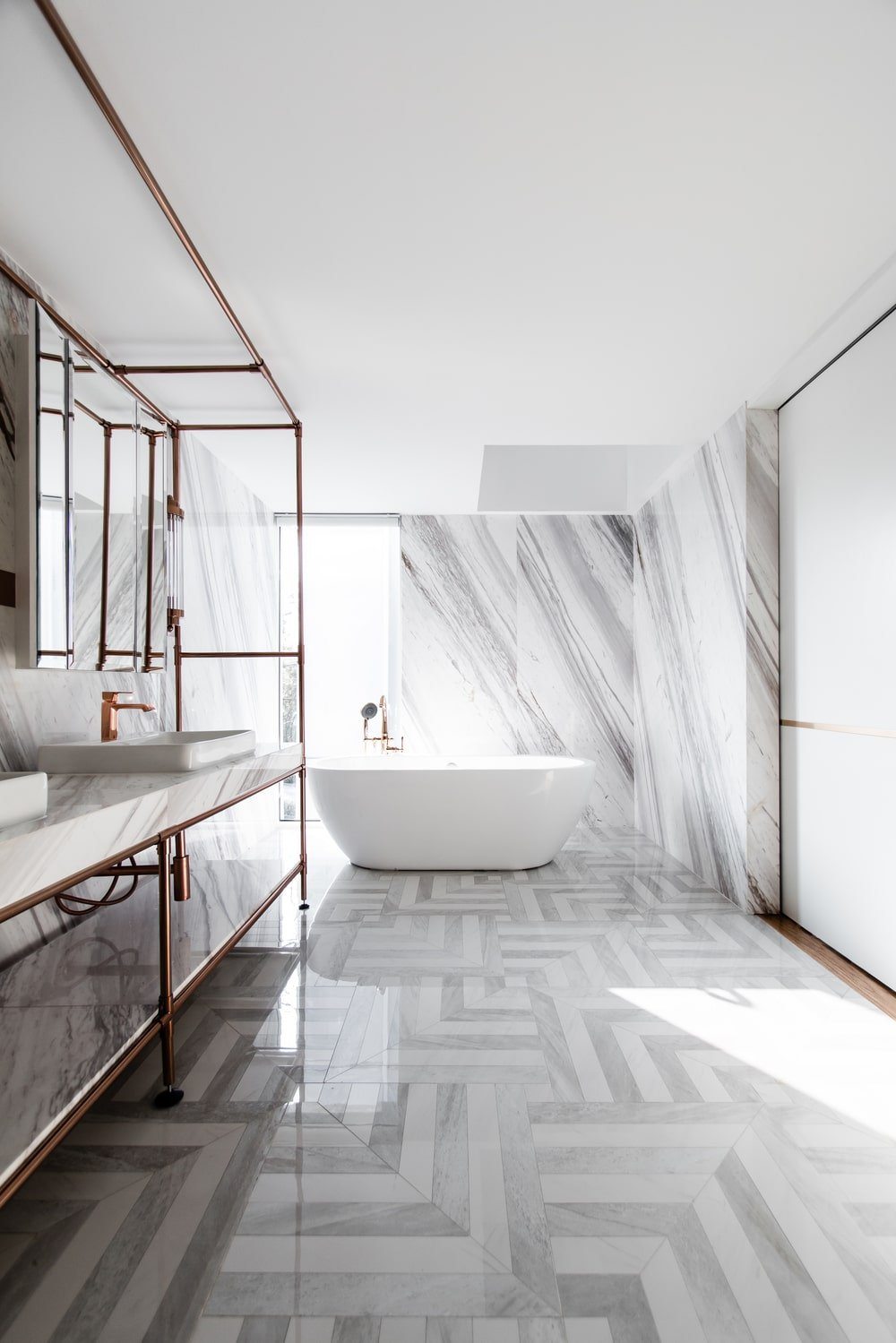 On the side of the large vanity area of the bathroom is the freestanding bathtub on the far side that stands out against the marble wall.