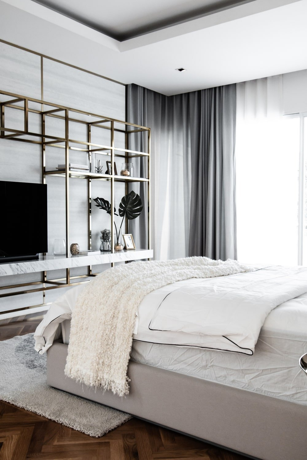 The bedroom has a golden mounted shelving system across from the bed.