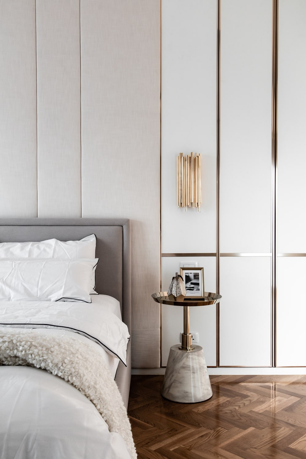 The bed also has small round bedside tables in a metallic tone to match the wall accents.