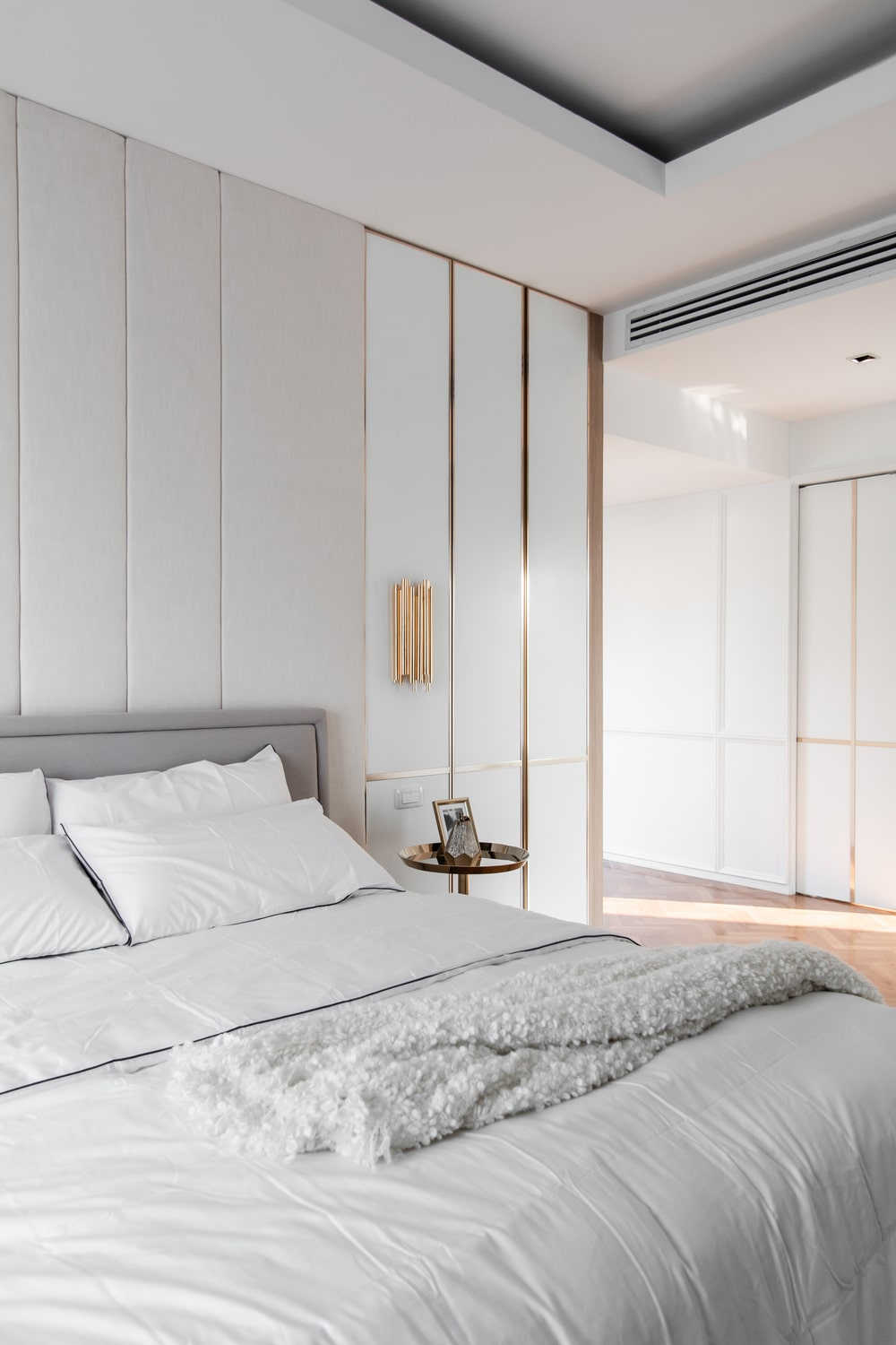The bedside table is then topped with a wall-mounted sconce.